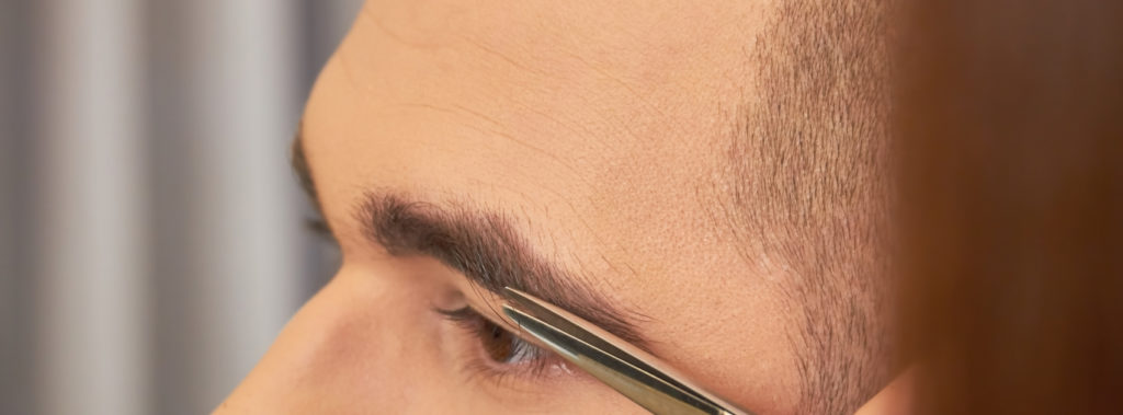 A man is getting his eyebrows trimmed by a pair of scissors, adding definition and shape.