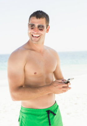 A man in swimming trunks standing on the beach smiling as he holds his phone. He is wearing sun-glasses.