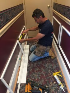 A contractor measures decorative fittings as he prepares to mount them on the walls.