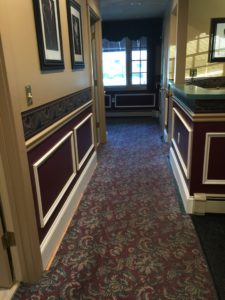 A newly renovated hallway with decorative wood framings, bump guard, and artwork on walls.