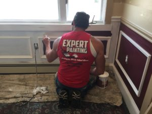 "A man in a red shirt reading ""Expert Painting"" applies a coa of paint on the baseboards and lower walls."