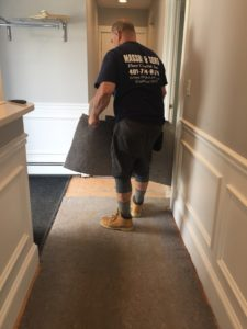 A man standing in a hallway with flooring in his hands, as he prepares to place it as part of renovations.
