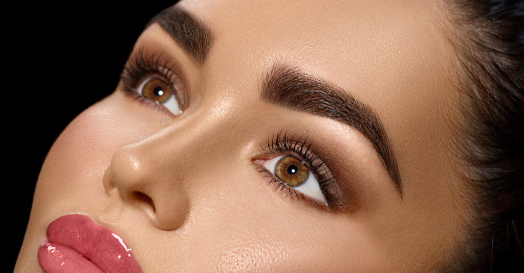 A close up view of shaped eyebrows on a womans face. The lines are sharp and crisp, and accented by eyeshadow and lashes.