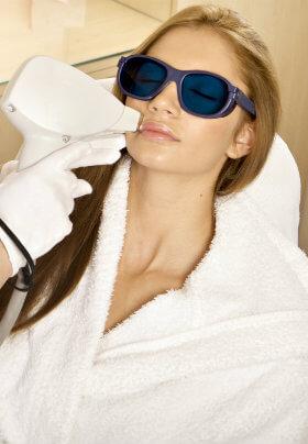 Woman in plush robe and sunglasses receiving a facial treatment in a salon/spa chair.