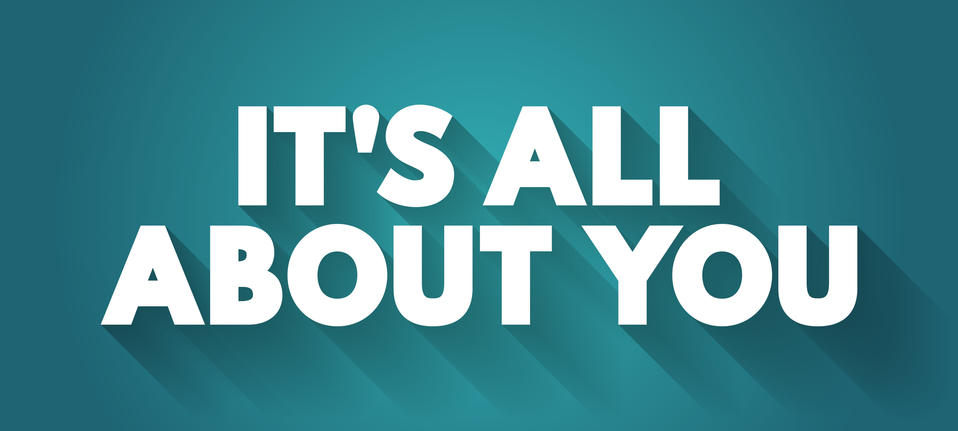 A man and woman with vibrant smiles pose underneath an umbrealla on a beach with billowing clouds above the water in the background.