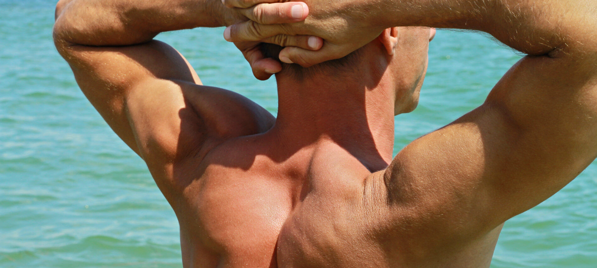 The sculpted muscular back of a shirtless man with his arms over his head lending definition to his lines.