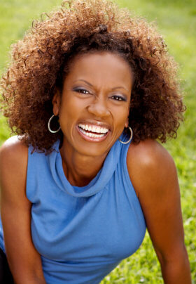 Woman with blue sleeveless blouse lounging on a grassy area with a large bright smile and bouncy hair.
