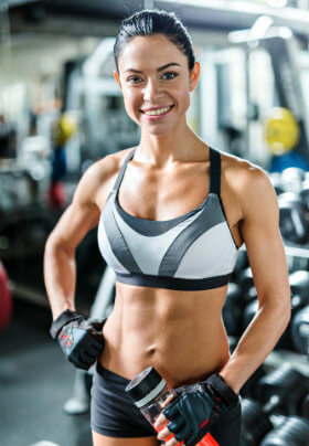 A smiling brunette woman in gym-wear with tied back hair as she pauses for a drink while working in a weight room.