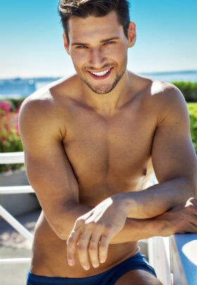 A man posing against an outside bar in his blue swimwear with a clear blue sky and waves in the background.