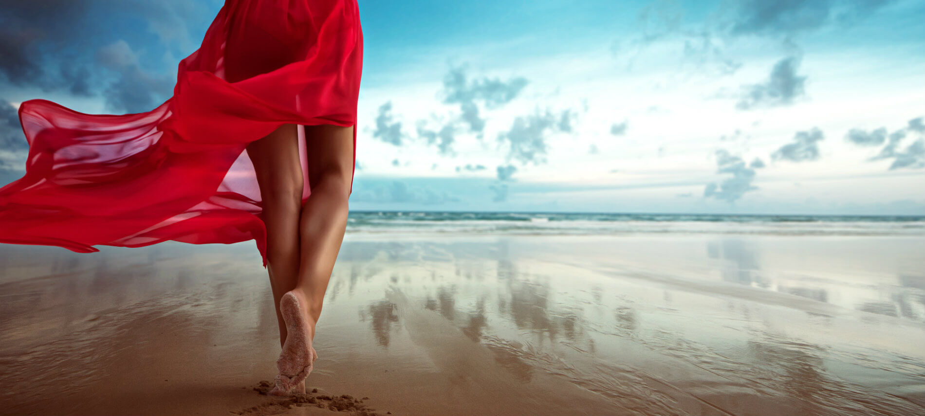 Rolling white clouds in the distance over a beach with a woman walking in a flowing red dress upon glistening bronze sand.