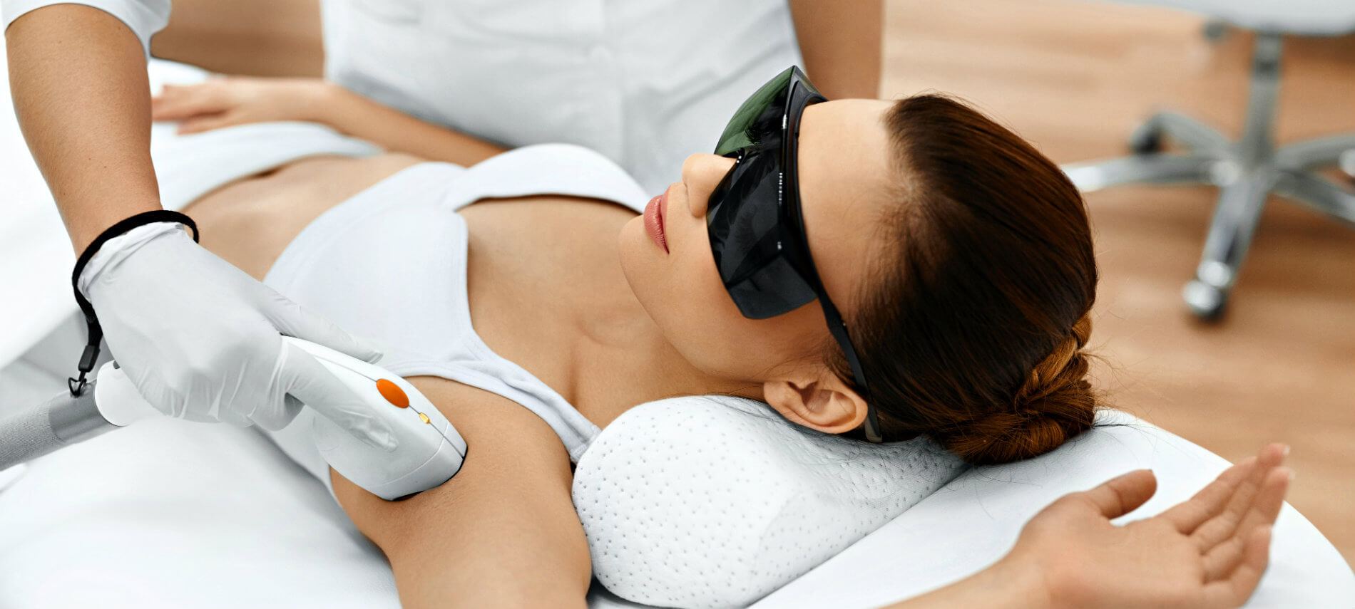 A woman in dark glasses receiving a hair treatment on her axila or armpit.