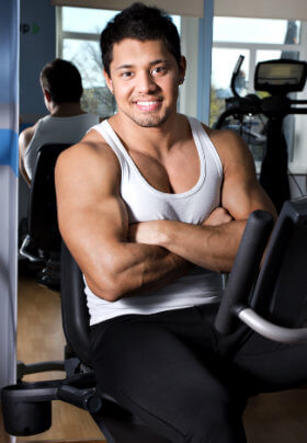 A man in shite muscle shirt sits on a piece of equipment with mirror in background posing/flexing his arms slightly in front of his smooth pecs.