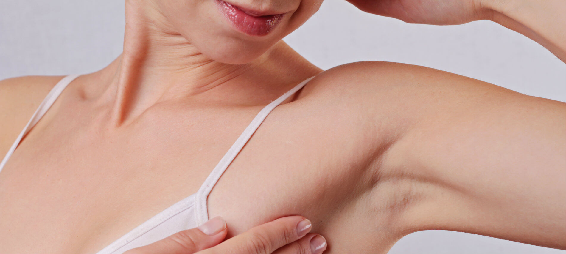 A woman holds the skin around her armpit as she examines the hair treatment and smooth skin.
