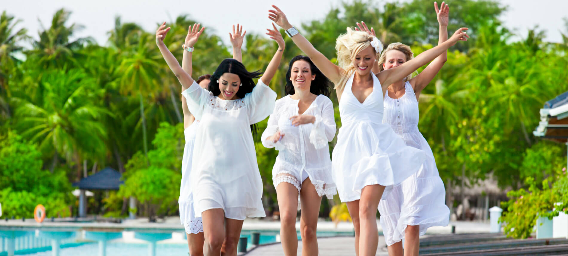 A group of women dressed in white summe wear, walking happily alongside a pool with their hands triumphantly in the air,