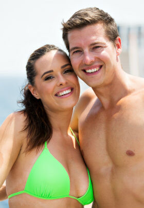 A man and woman embracing as they smile for the camera showing off well defined and hairless bodies.